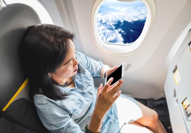 Vue de dessus de femme asiatique assis au siège de la fenêtre dans l'avion et en mode avion