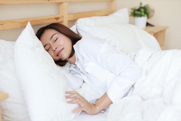 Vue de dessus femme asiatique belle et en bonne santé dormant sur un lit blanc dans la chambre