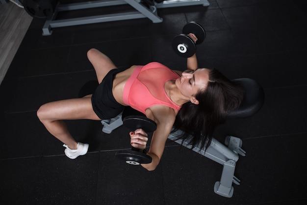 Vue de dessus d'une femme athlétique faisant du développé couché avec haltères