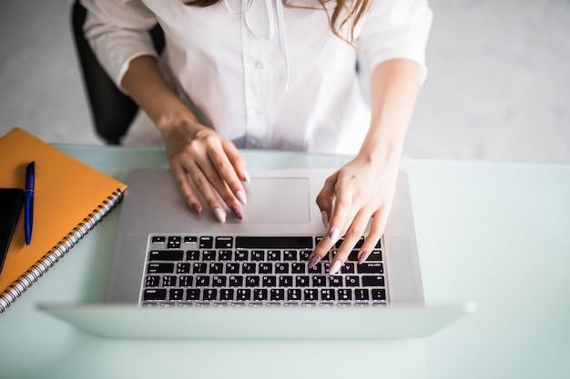 Vue de dessus de la femme de bureau pendant son travail sur ordinateur portable dans un bureau léger moderne