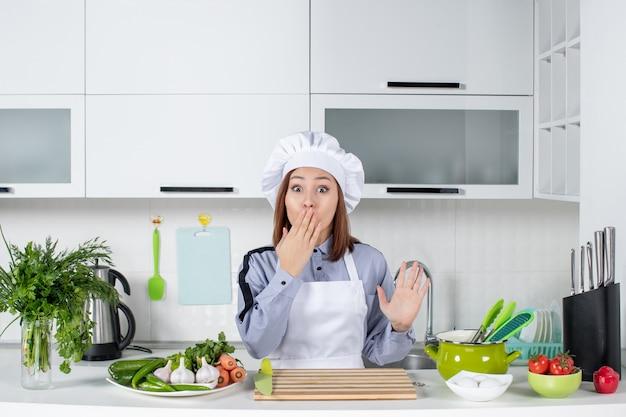 Vue de dessus d'une femme chef choquée et de légumes frais dans la cuisine blanche