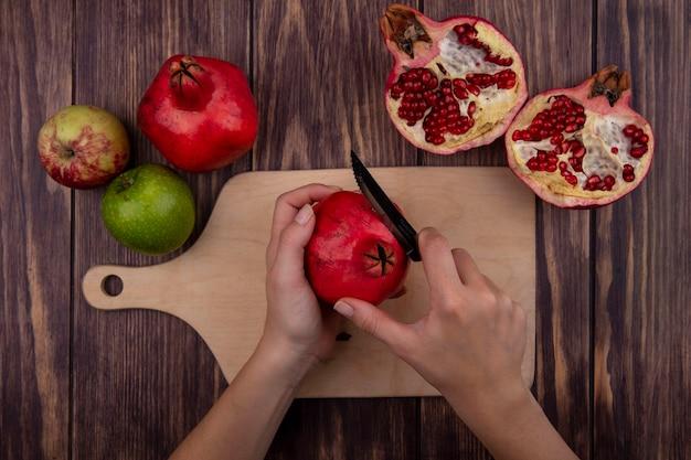 Vue de dessus femme coupe la grenade sur une planche à découper avec des pommes sur un mur en bois