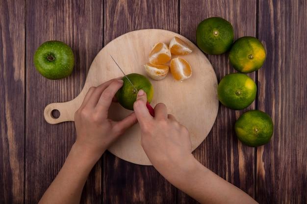 Vue de dessus femme coupe les mandarines vertes sur une planche à découper sur un mur en bois