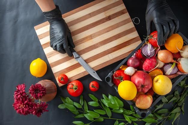 Vue de dessus femme cuisinier coupant des légumes sur une surface sombre