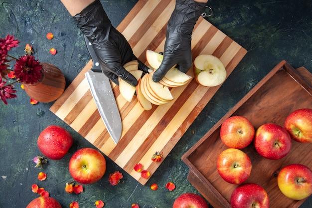 Vue de dessus femme cuisinier coupant des pommes sur la surface grise