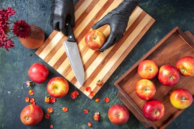 Vue de dessus femme cuisinier coupant des pommes sur une surface sombre