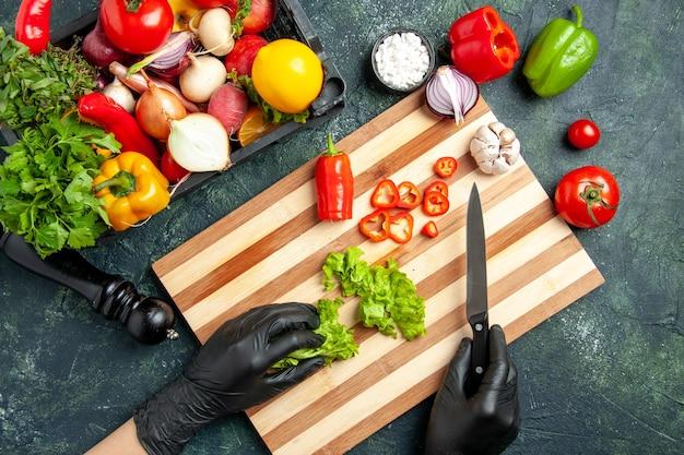 Vue de dessus femme cuisinier coupant la salade verte fraîche sur la surface grise