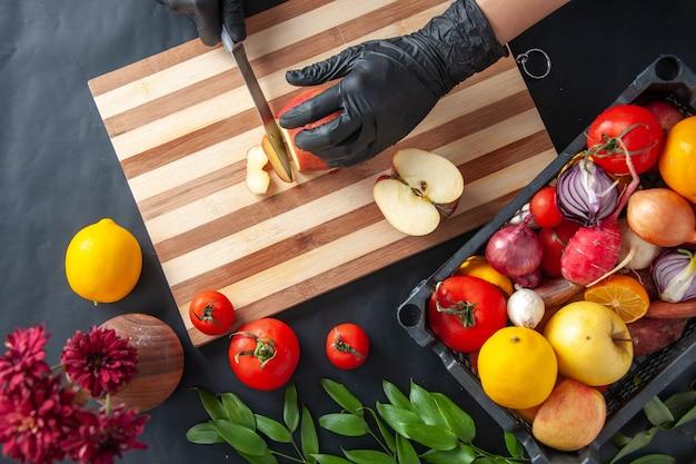 Vue de dessus femme cuisinier coupe pomme sur la surface sombre