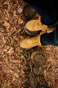 Vue de dessus femme debout avec des bottes de montagne de randonnée sur les feuilles d'automne et fond de bois