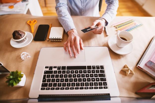 Vue de dessus d'une femme designer achetant en ligne avec la carte tout en étant assis dans le beau bureau lumineux.