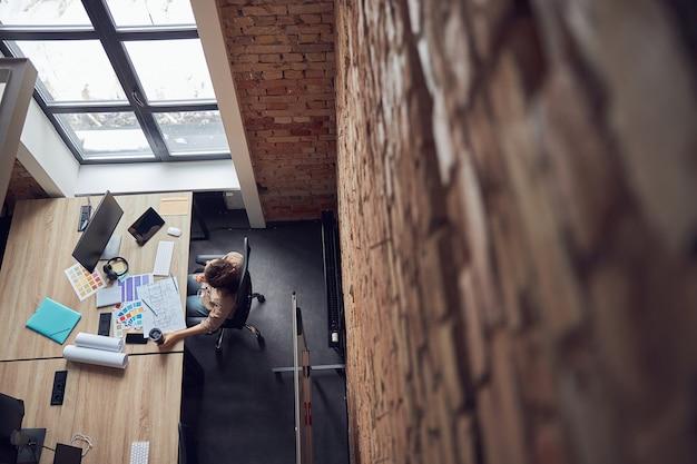 Vue de dessus d'une femme designer lisant un plan tout en travaillant sur un nouveau design d'intérieur