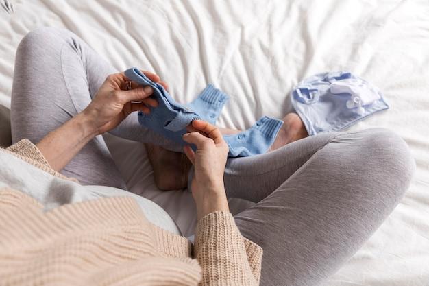 Vue de dessus femme enceinte avec des vêtements pour bébé