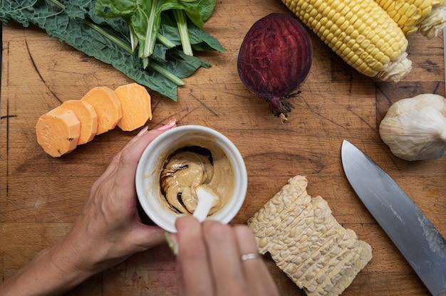 Vue de dessus d'une femme faisant vinaigrette végétalienne dans une tasse sur une planche à découper en bois pleine de divers légumes d'automne et de protéines de tempeh.