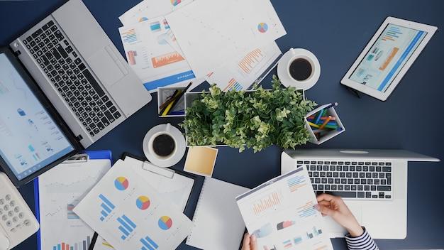 Vue de dessus d'une femme gestionnaire analysant l'expertise de frappe de stratégie de paperasse financière sur un ordinateur portable