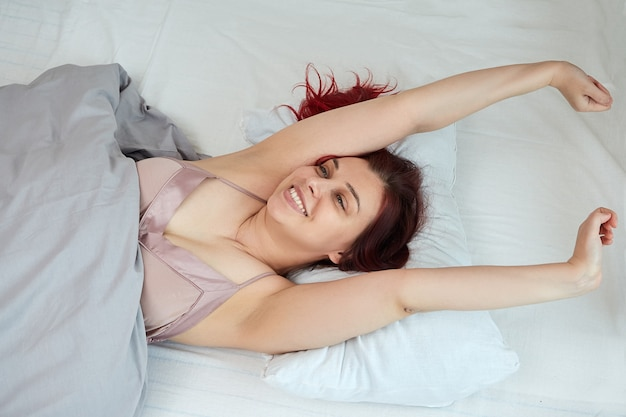 Vue de dessus d'une femme heureuse en haut rose se réveillant allongée dans son lit qui s'étire.