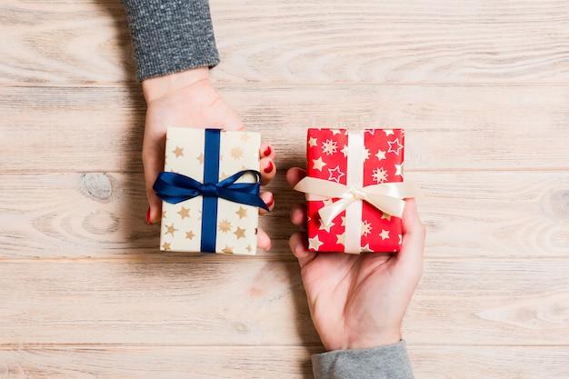 Vue de dessus d'une femme et un homme échangeant des cadeaux sur bois. couple donne des cadeaux les uns aux autres.