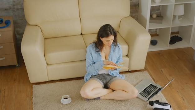 Vue de dessus d'une femme en jeans courts lisant un livre avec une tasse de café et un ordinateur portable à côté d'elle