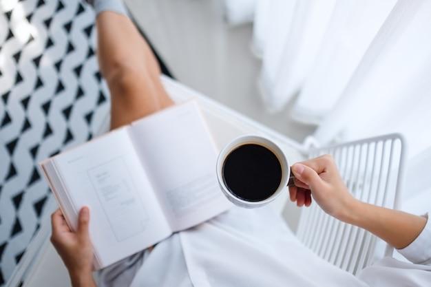 Vue de dessus d'une femme lisant un livre et buvant du café chaud dans la chambre à la maison le matin