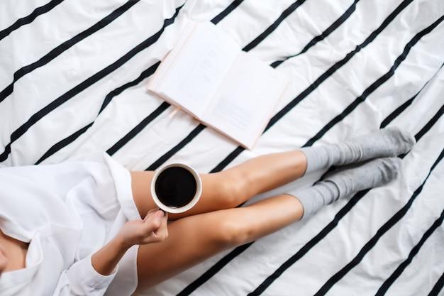 Vue de dessus d'une femme lisant un livre et buvant du café chaud dans un lit confortable blanc à la maison le matin