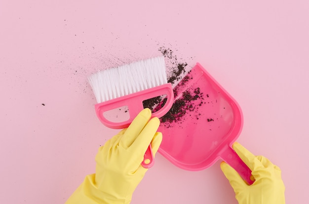 Vue de dessus femme mains dans des gants en latex jaune avec brosse et pelle