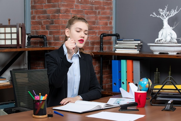 Vue de dessus d'une femme nerveuse assise à une table et tenant du papier emballé au bureau