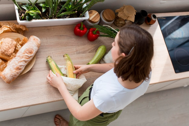Vue de dessus femme organisant des produits d'épicerie bio