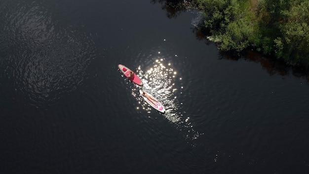 Vue de dessus femme paddle sup surfant sur la rivière. concept détente et vacances. vue de dessus des touristes sur le lac avec des planches de sup. belle eau claire avec des gens flottant sur des planches en sup-surf