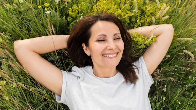 Vue de dessus de la femme posant dans l'herbe à l'extérieur