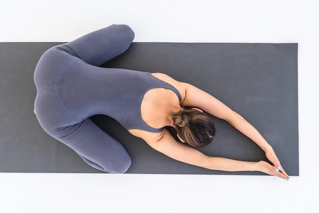 Vue de dessus d'une femme pratiquant le yoga allongée sur un tapis dans une pose relaxante sur fond blanc en studio