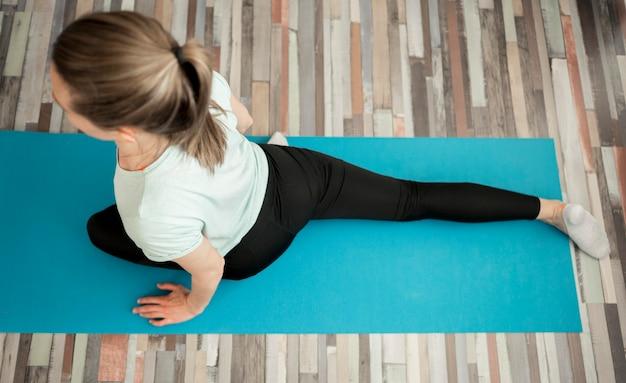 Vue de dessus femme pratiquant le yoga à la maison