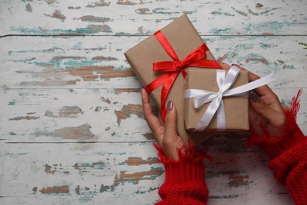 Vue de dessus femme en pull rouge tenant des coffrets cadeaux de noël sur fond de bois.