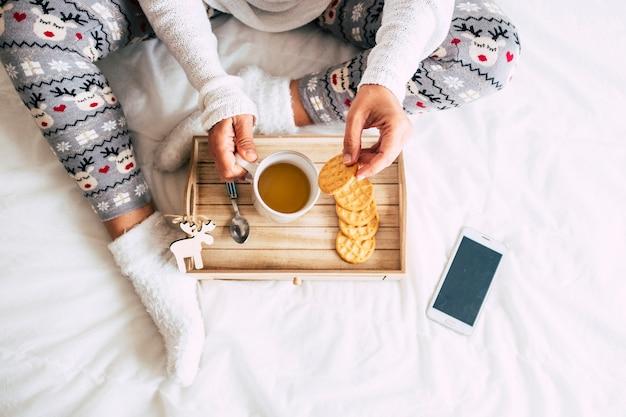 Vue de dessus d'une femme de race blanche faire le petit déjeuner au lit sur une couverture blanche