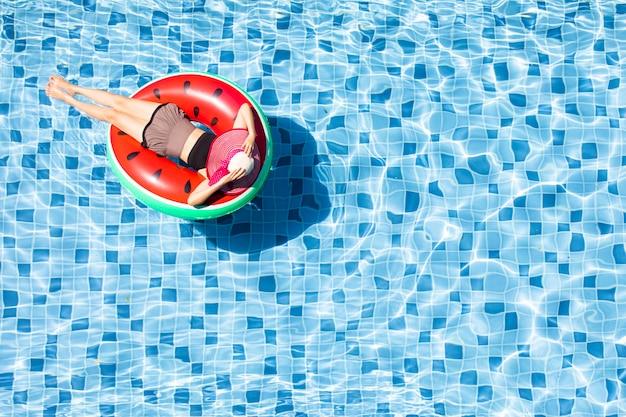 Vue de dessus de la femme s'étendent sur le ballon dans la piscine