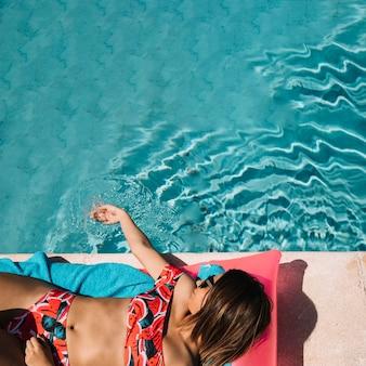Vue de dessus de la femme se détendre à côté de la piscine