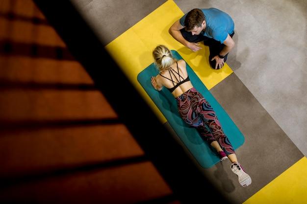 Vue de dessus à la femme sportive exerce avec l'aide de son entraîneur personnel
