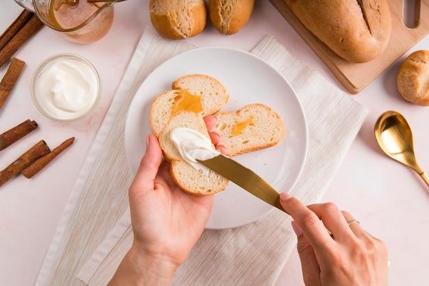 Vue de dessus femme tartinade de fromage à la crème sur du pain