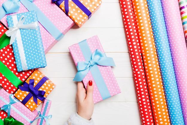 Vue de dessus d'une femme tenant une boîte-cadeau dans ses mains sur un fond en bois festif
