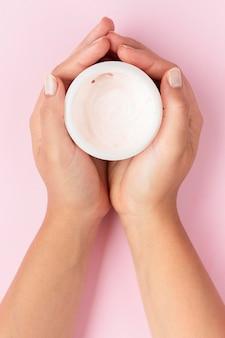Vue de dessus femme tenant une boîte de crème pour le visage