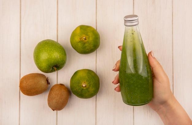 Vue de dessus femme tenant une bouteille de jus avec pomme kiwi et mandarines sur mur blanc
