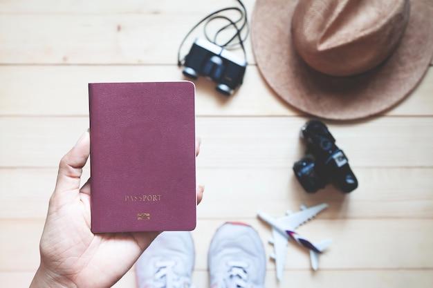 Vue de dessus femme tenant livre passeport avec appareils photo et un chapeau sur un plancher en bois.
