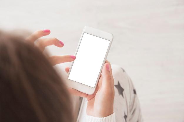 Vue de dessus de la femme tenant la maquette verticale de téléphone intelligent moderne avec un tracé de détourage