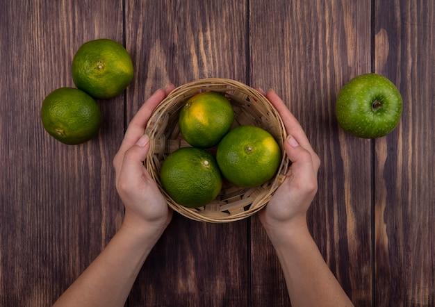 Vue de dessus femme tenant panier avec mandarines vertes et pomme sur mur en bois