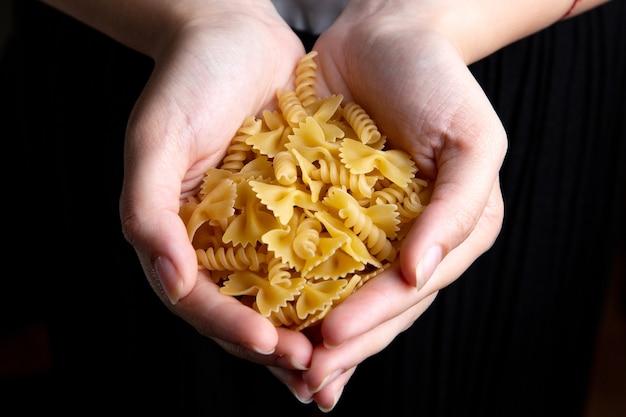 Une vue de dessus femme tenant des pâtes alimentaires crues et jaunes pâtes italiennes