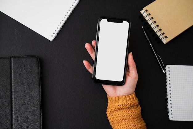 Vue de dessus femme tenant un smartphone vide