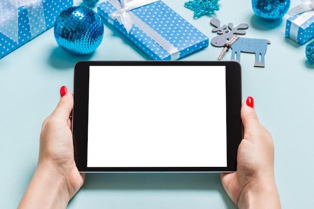 Vue de dessus de la femme tenant la tablette dans ses mains sur fond bleu fait de décorations de noël.