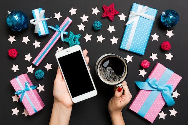 Vue de dessus d'une femme tenant un téléphone dans une main et une tasse de café dans une autre main en noir.