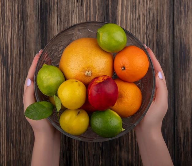 Vue de dessus femme tenant un vase avec mélange de fruits pamplemousse oranges limes prune et pêche sur fond de bois