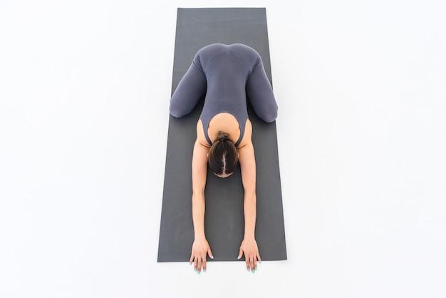 Vue de dessus d'une femme yogi pratiquant le yoga sur un tapis faisant une pose relaxante