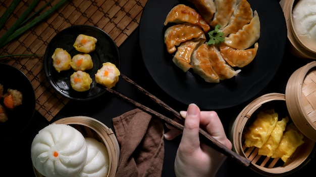 Vue de dessus des femmes mangeant des dim sum avec des boulettes, des petits pains et du gyoza dans un restaurant chinois