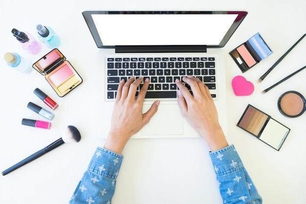 Vue de dessus des femmes utilisant un ordinateur portable pour rechercher des informations cosmétiques pour le maquillage, le concept de beauté.